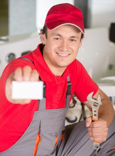 配管工は手でスパナを保持していると名刺を表示 Premium写真