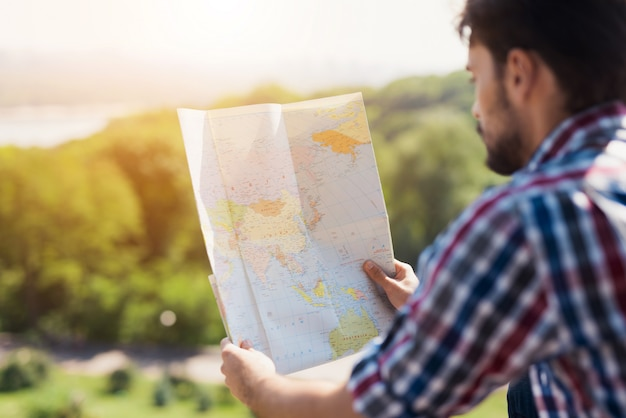 流行に敏感な観光客が地図を勉強して一人でハイキングします。 Premium写真