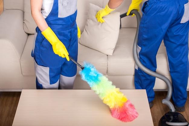 若いカップルのプロの洗剤が家を掃除しています。 Premium写真