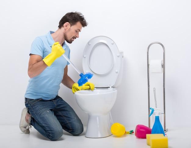 若い男がプランジャーでトイレの目詰まりを解消します。 Premium写真