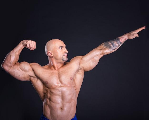 ボディービルダーはポーズをとって、彼の筋肉を見せています。 Premium写真