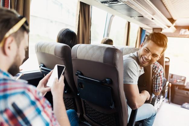 男はバスに乗っています。彼は向きを変えて乗客を見た。 Premium写真