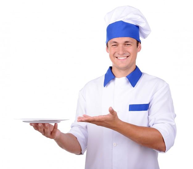 Шеф-повар в форме, вручая белые пластины, изолированные на белом. Premium Фотографии