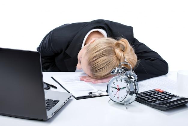 彼のラップトップの横に眠っている疲れ若いビジネス女性。 Premium写真