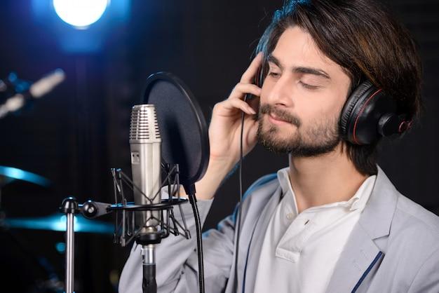 Молодой человек записывает песню в профессиональной студии. Premium Фотографии