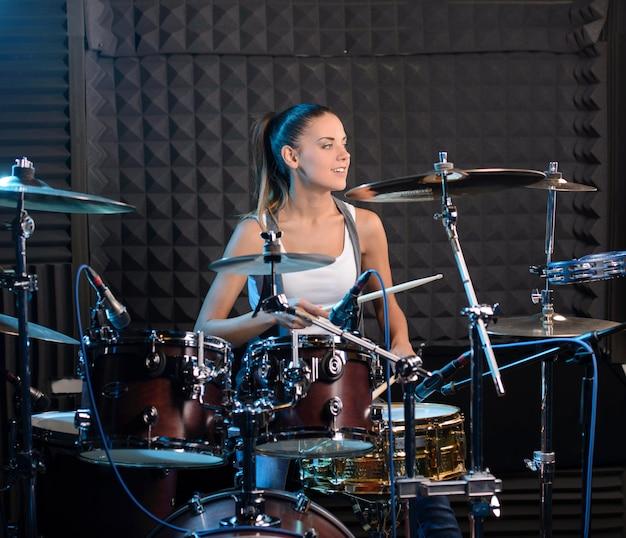 プロのスタジオでのドラム式インスタレーションの背後にある女の子。 Premium写真