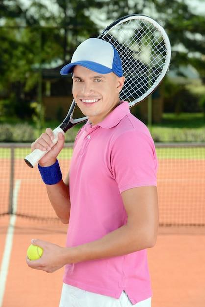 テニス選手がテニスコートの前でポーズします。 Premium写真
