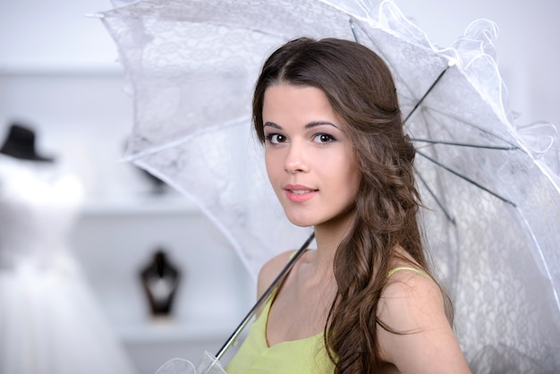 店で傘を持って立っている美しい女の子。 Premium写真