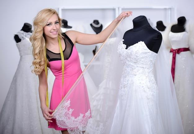 デザイナーのウェディングドレス、マネキンのドレスを測定します。 Premium写真