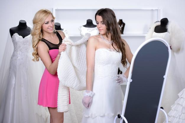 売り手は買い手がウェディングドレスを選ぶのを助けます。 Premium写真