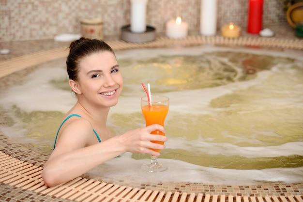 若い女性はキャンドルで泡風呂を浴びます。 Premium写真