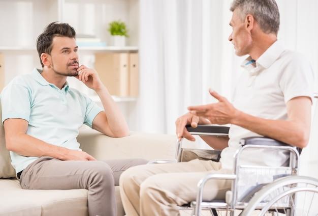 大人の男が家で座っていると彼の長老の父親に話しています。 Premium写真
