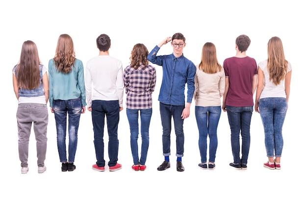 カメラに背を向けて若いグループ立っています。 Premium写真