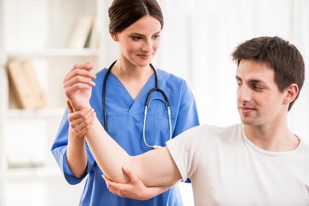 Физиотерапевт, массируя руку пациента мужского пола. Premium Фотографии