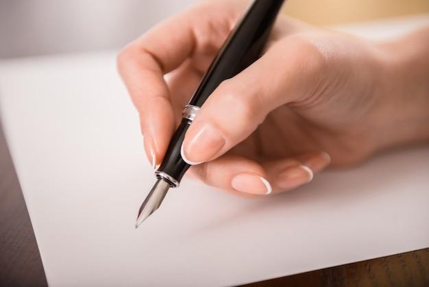 女性の手のクローズアップは紙に書いています。 Premium写真