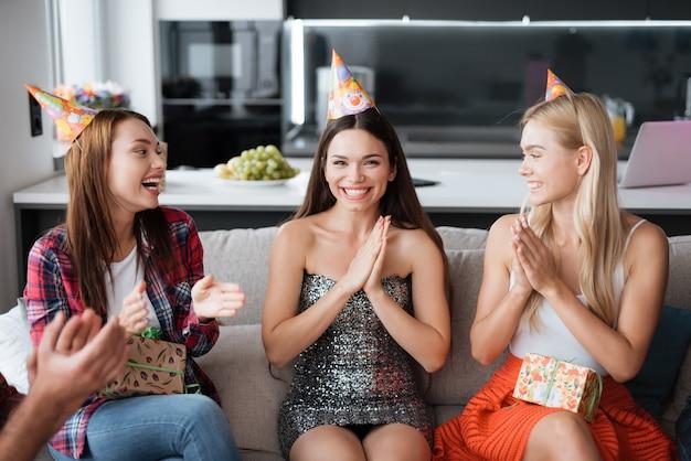 誕生日帽子の誕生日の女の子。ゲストの笑顔 Premium写真