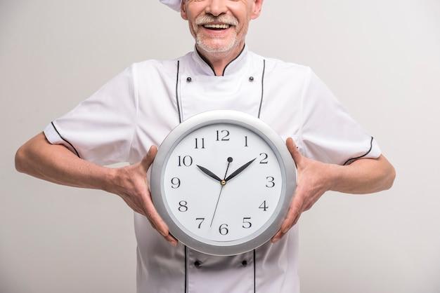 Старший мужской главный повар в форме проведения часов. Premium Фотографии