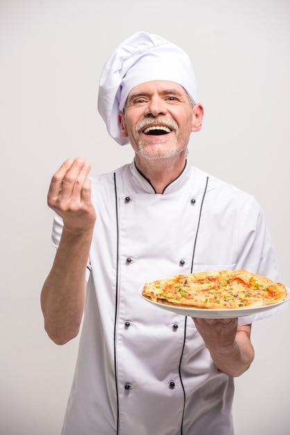 ピザを保持している制服を着た上級男性チーフ料理人。 Premium写真