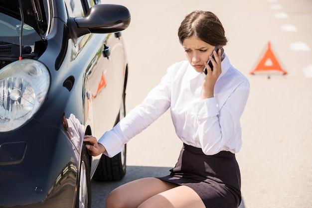 実業家の車の近くに座っていると電話で助けを求めて Premium写真