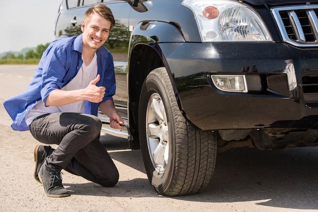 若い男が彼の車にパンクしたタイヤを変更します。 Premium写真