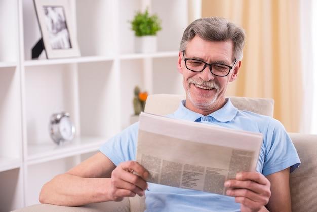 Старший мужчина читает газету у себя дома. Premium Фотографии