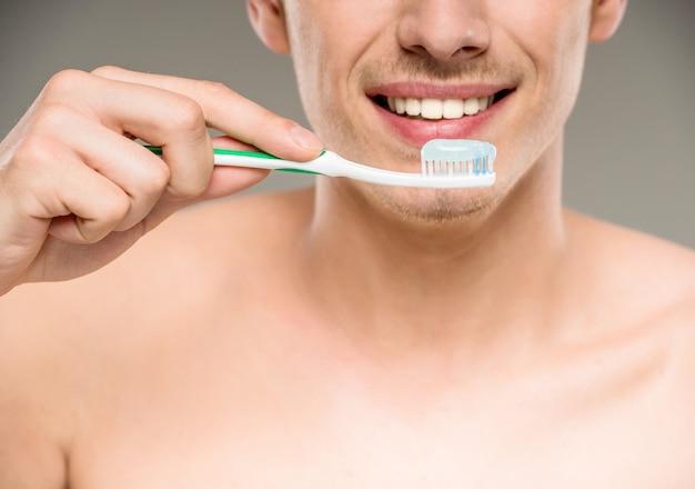 ハンサムな男が浴室で歯ブラシで歯を掃除します。 Premium写真
