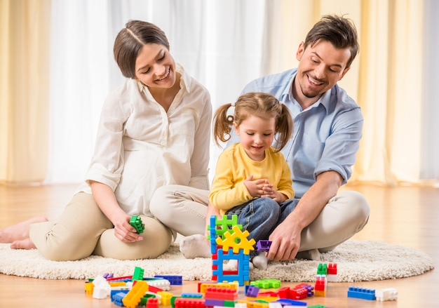 Беременная мать и молодой отец играет с дочерью. Premium Фотографии