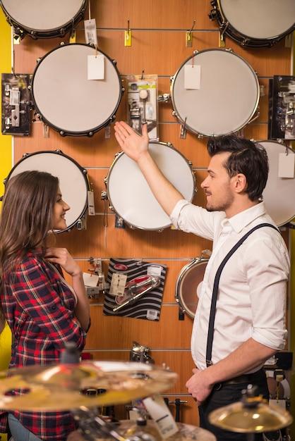 若い男がミュージックストアで女の子のドラムを見せています。 Premium写真