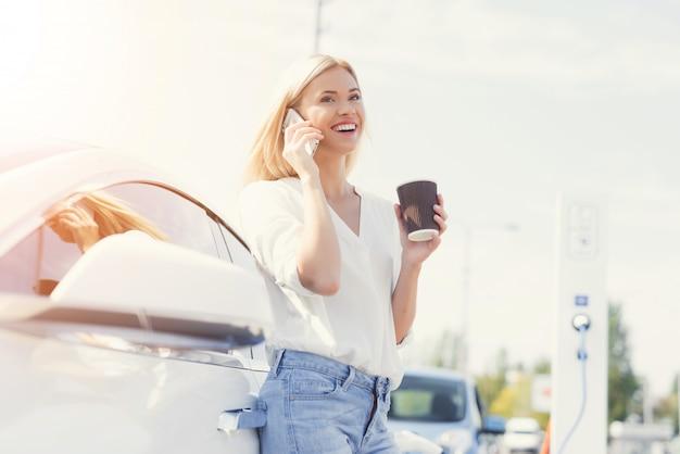 電話で話している若い幸せな女性ドライバー Premium写真