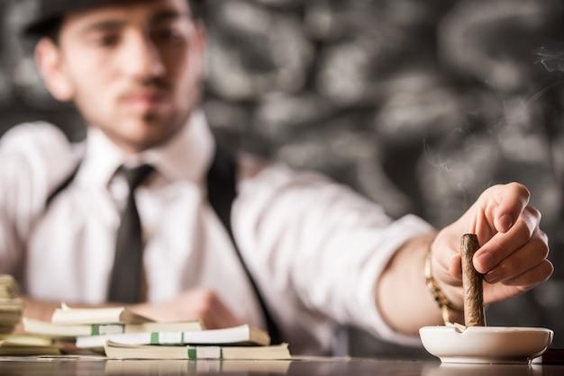 Уверенный гангстер человек курит кубинскую сигару. Premium Фотографии