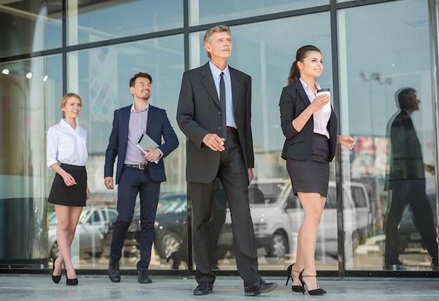 スーツを着た成功したビジネスマンが一緒に前進します。 Premium写真