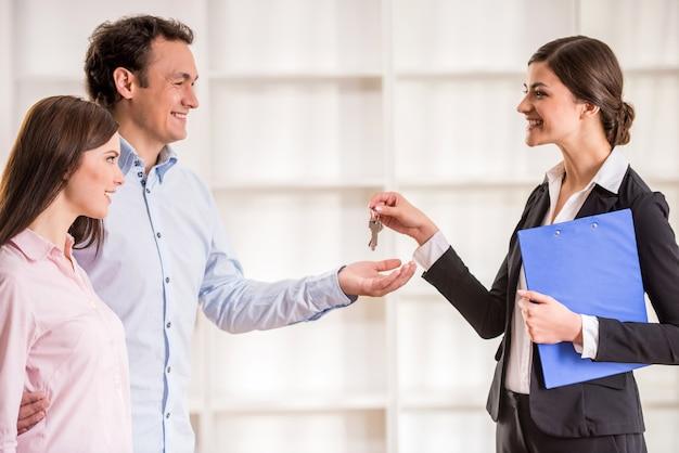 女性の不動産屋は新しいアパートから若いカップルの鍵を与えています。 Premium写真