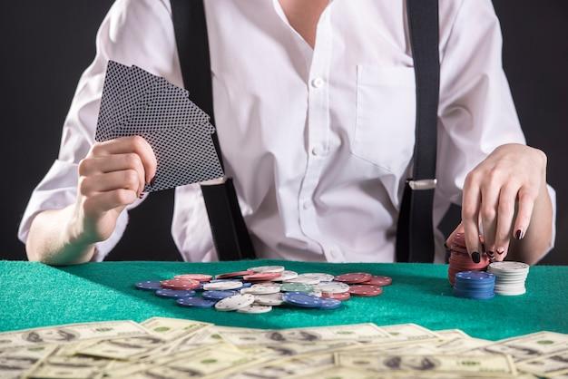 Молодой женский гангстер играть в покер в казино. Premium Фотографии