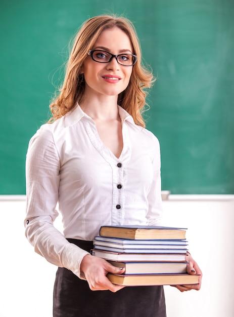 先生は教室で本を持っています。 Premium写真