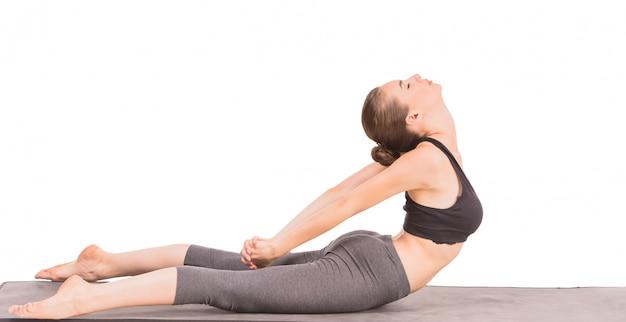 猫のポーズでヨガの練習をしているスポーティな女性。 Premium写真