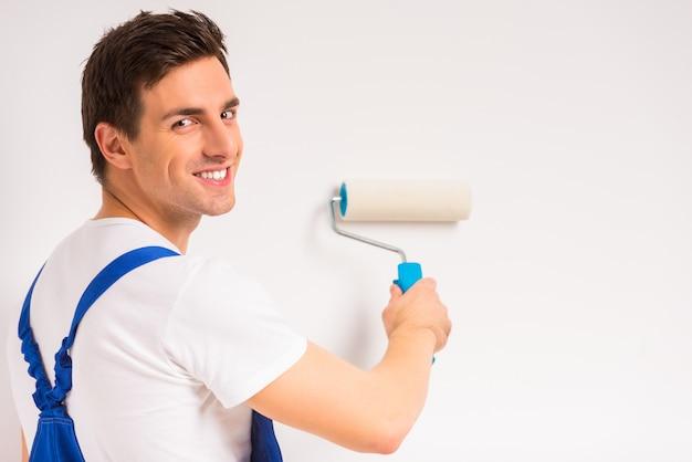 Мужчина рисует белую стену и улыбается. Premium Фотографии