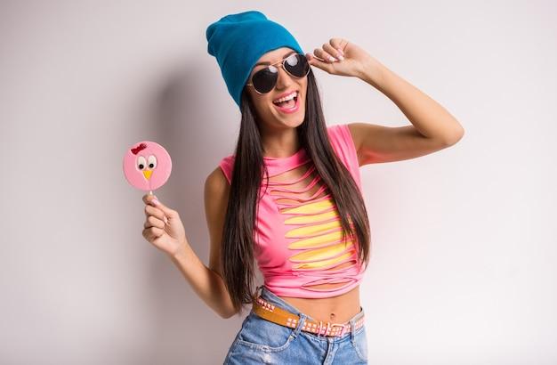 Молодая стильная усмехаясь женщина в голубой крышке и солнечных очках. Premium Фотографии