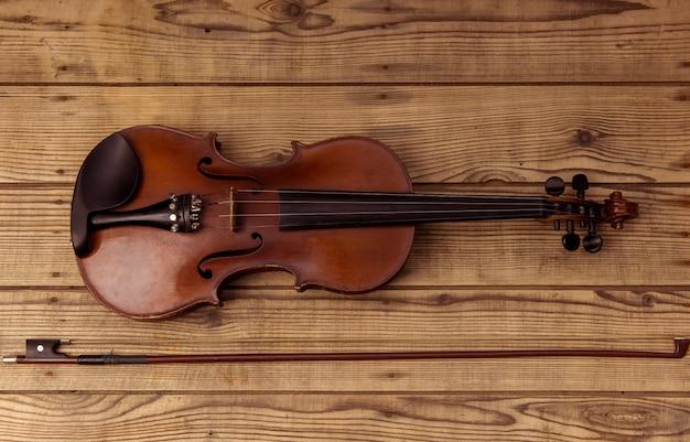 ヴァイオリンは木のテーブルの上に横たわるをクローズアップ。 Premium写真