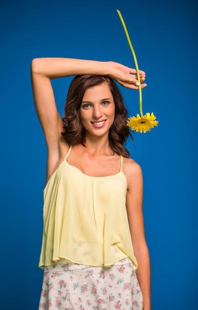 黄色の花を持つ若い女 Premium写真