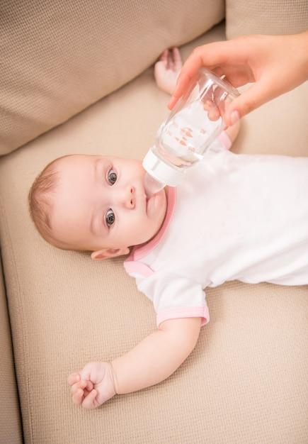 母はボトルから彼女の愛らしい娘を供給します。 Premium写真
