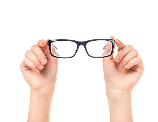 女性の手が分離されたメガネを保持します。 Premium写真