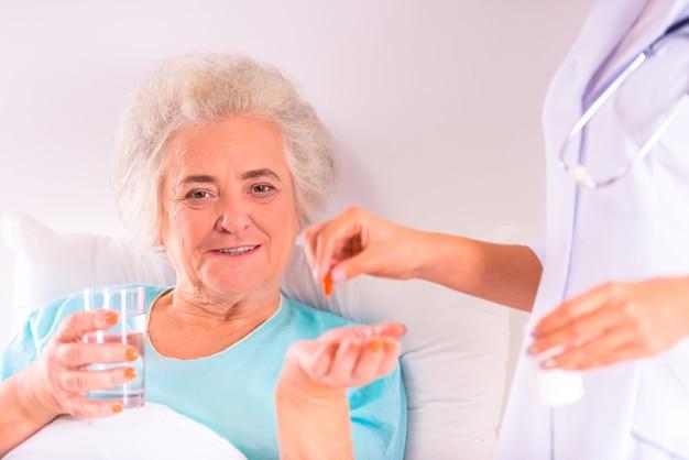 看護師はベッドで高齢の祖母に薬を与えます。 Premium写真