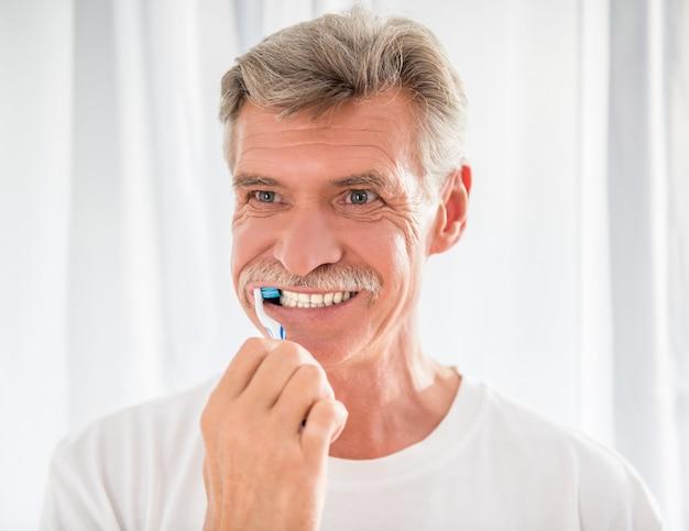年配の男性人は彼の歯をきれいにして笑っています。 Premium写真
