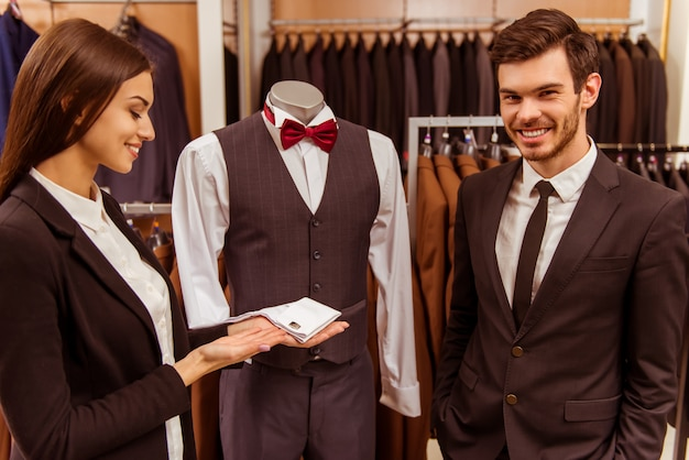 その少女はスーツの隣に立っていて笑っています。 Premium写真