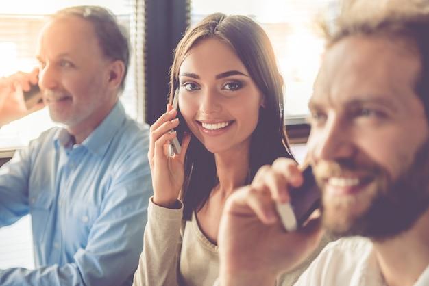 Красивые деловые люди разговаривают по мобильным телефонам. Premium Фотографии