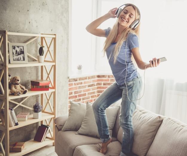 ヘッドフォンで美しい少女は音楽を聴いています。 Premium写真