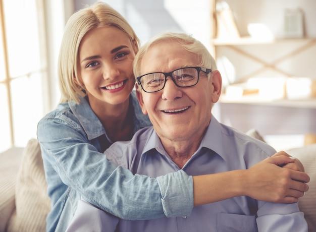 ハンサムな老人と美しい少女が抱いています。 Premium写真