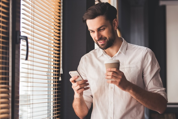 Красивый молодой бизнесмен использует смартфон. Premium Фотографии