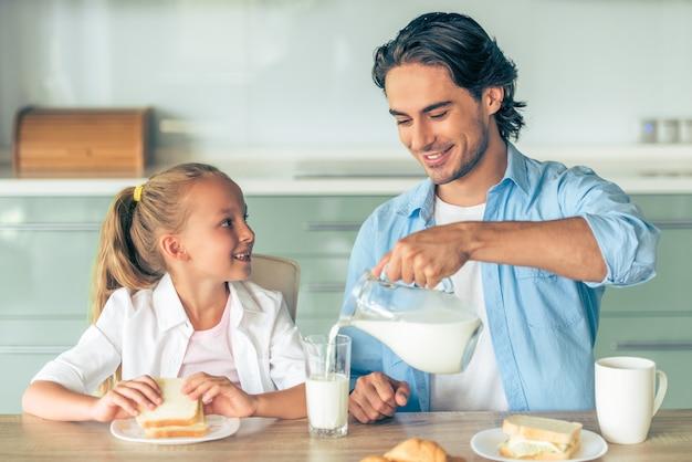 Милая маленькая девочка ест бутерброд на завтрак. Premium Фотографии