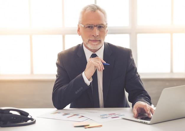 Бизнесмен в классическом костюме и очках использует ноутбук Premium Фотографии